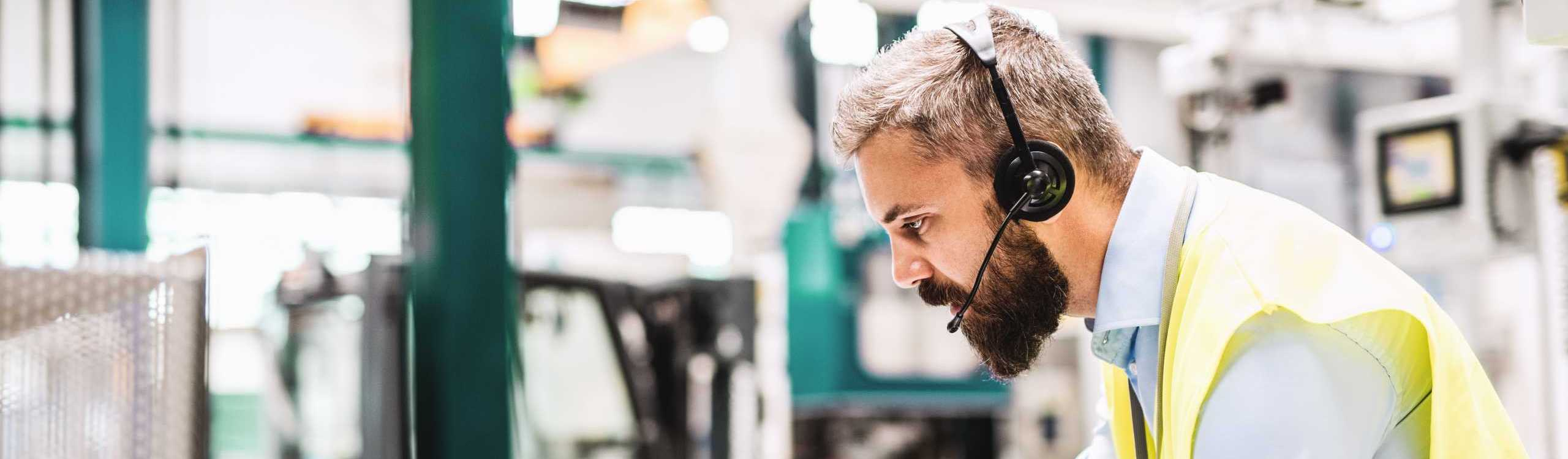 Engineer with a headset is working in a large industrial hall