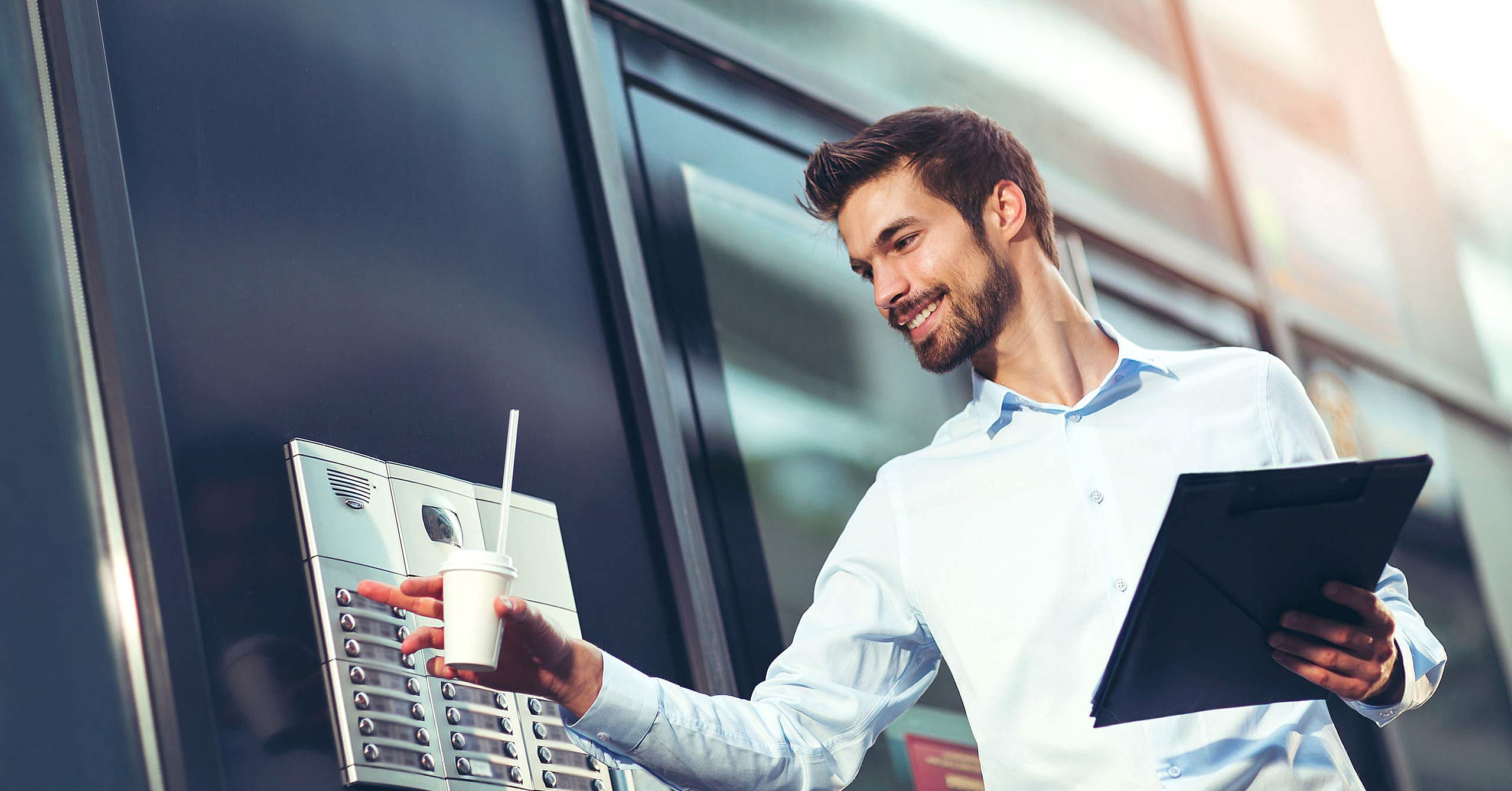 Portrait of a young happy businessman who is ringing the bell at a intercom